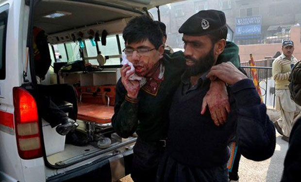 A hospital security guard helps a student injured in the shootout at a school under attack by Taliban gunmen in Peshawar, Pakistan,Tuesday, Dec. 16, 2014. Taliban gunmen stormed a military school in the northwestern Pakistani city, killing and wounding dozens, officials said, in the latest militant violence to hit the already troubled region.