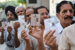 Indian voters hold up their voter ID car